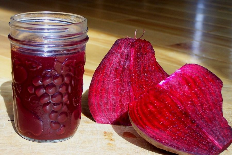 A fresh beet and a jar of fermented beet juice