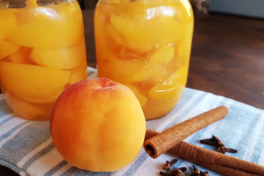 A peach, cinnamon sticks and canned peaches