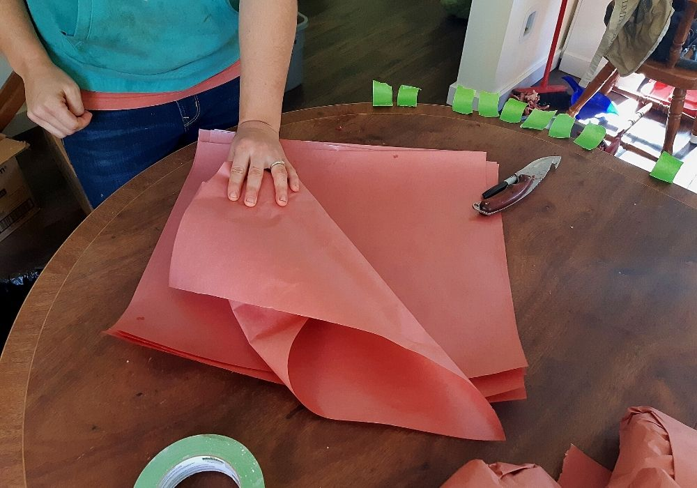 folding in the bottom and edge of the butcher paper