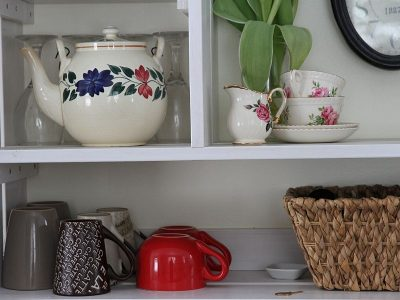 Open shelving in kitchen displaying tea cups, tea pot and a basket
