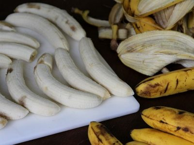 Freshly peeled bananas on a cutting board