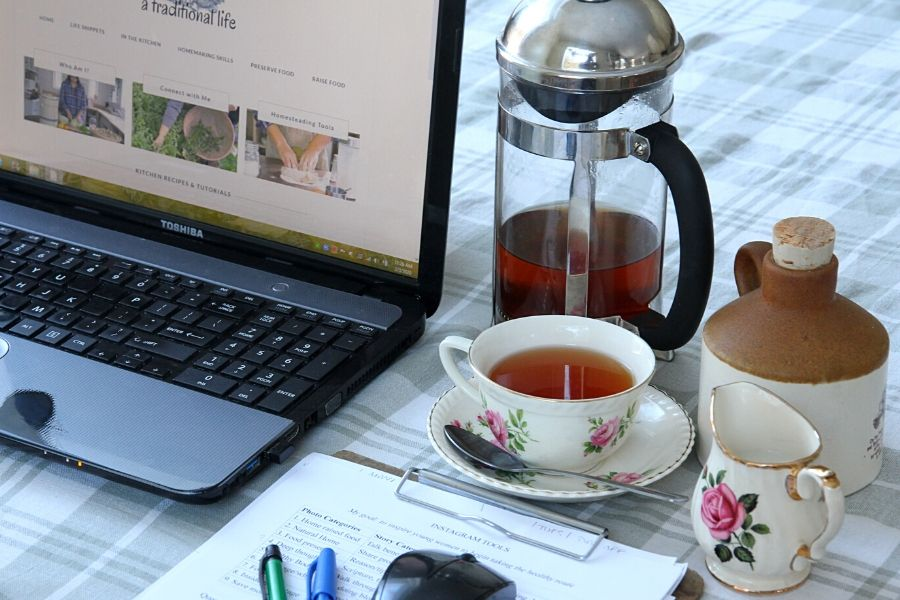 tea, a french press, laptop and clipboard