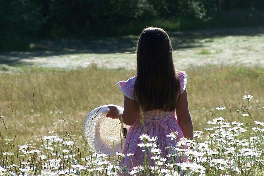 A little girl holding a sunhat in hayfield