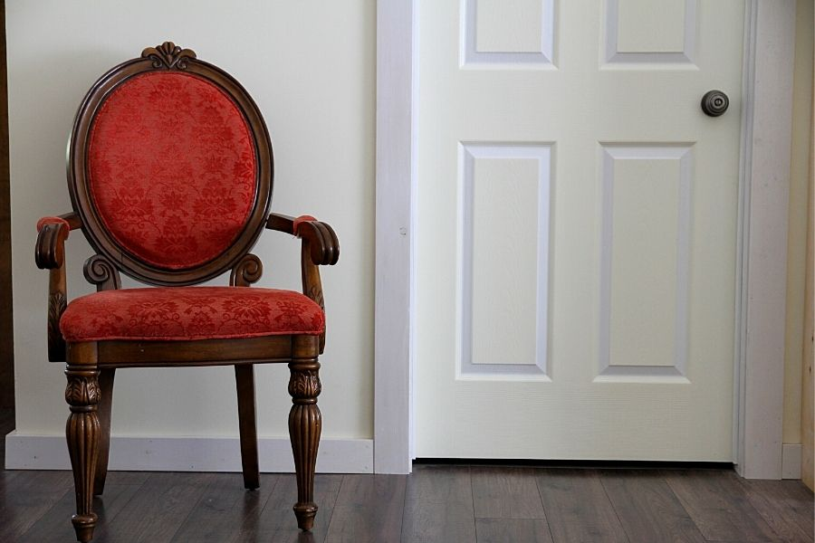 A red armchair next a cream and white, painted door