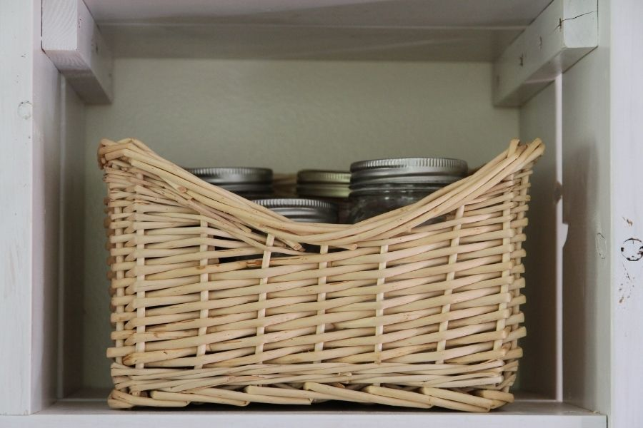 a square basket on an open shelf with jars inside