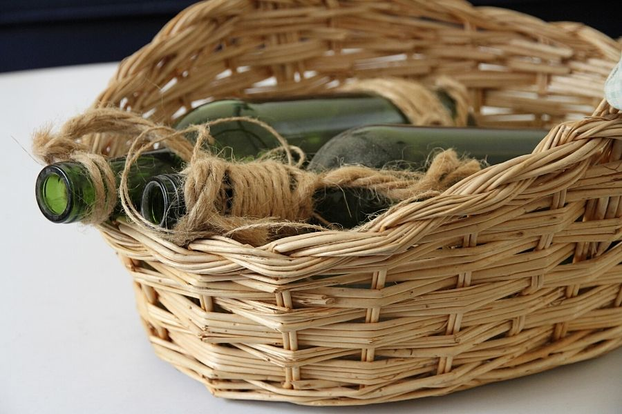 a basket holding two green bottles