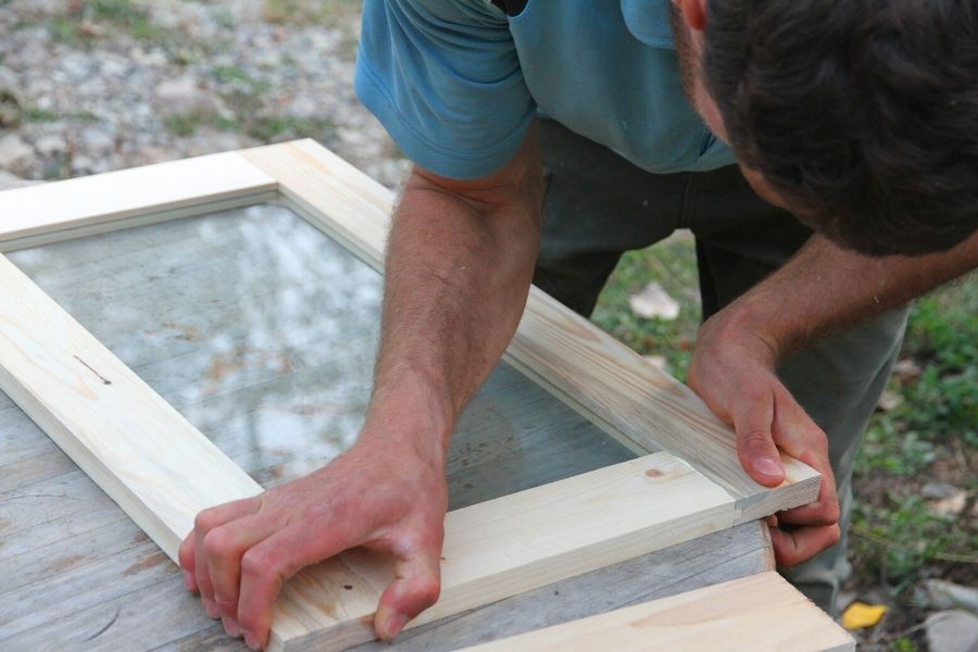 a man setting glass into a wooden frame