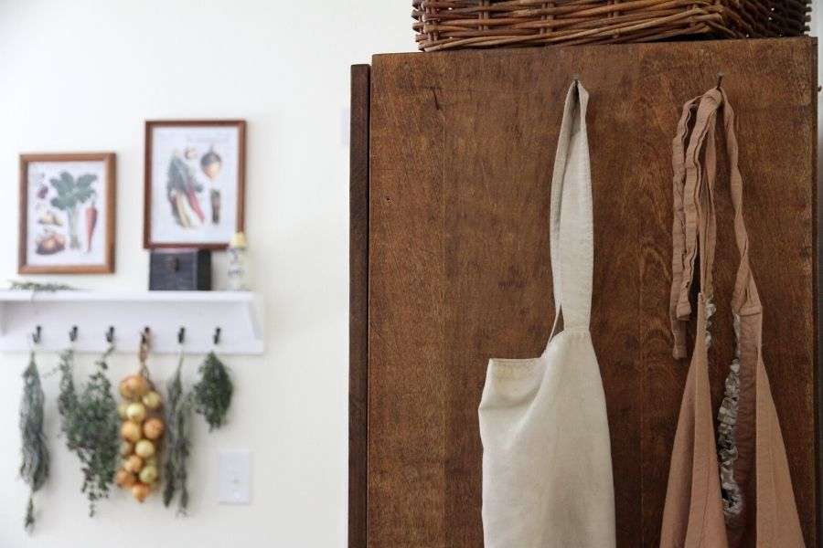 aprons hanging from nails on the end of a dining room hutch