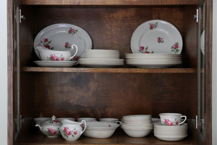 a flowered china set arranged on two shelves