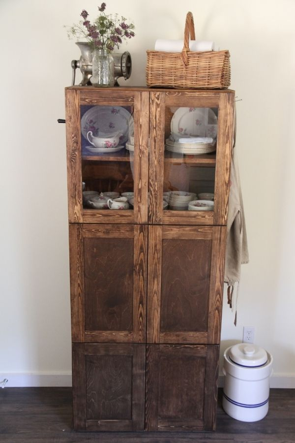 a diningroom hutch with glass doors on the top