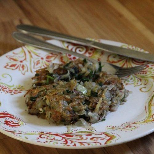 a plate, fork and knife with a crispy fried potato patty