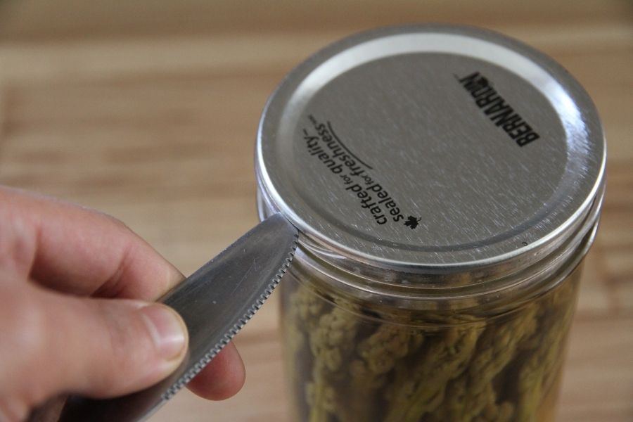 gently removing a lid from a jar of pickled asparaug using a butter knife