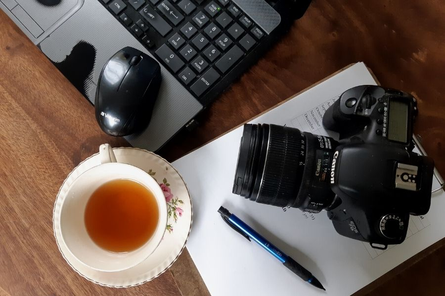 A blogger's workspace on a the kitchen table with computer, camera and a cup of tea