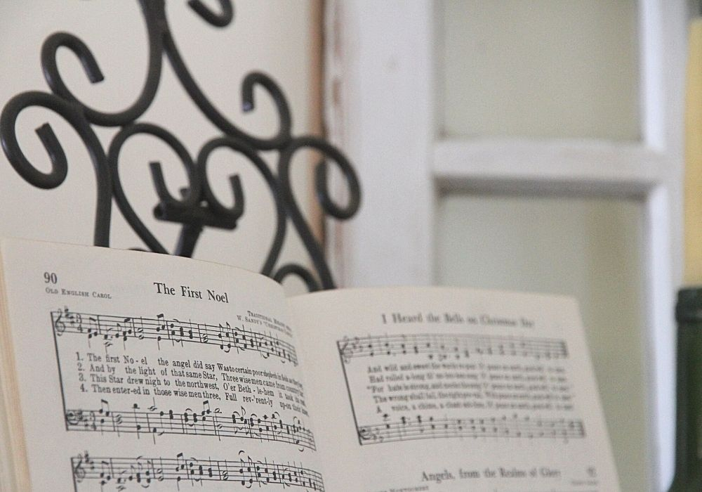An open hymnal displayed on a black book holder