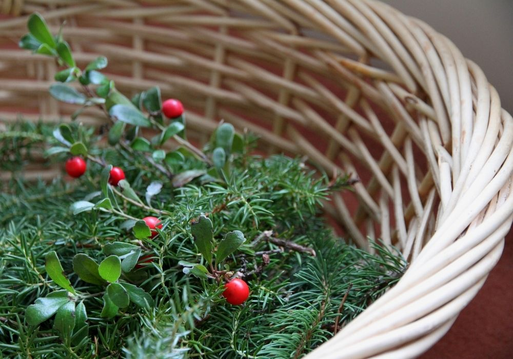 a woven basket filled with greenery and red berries