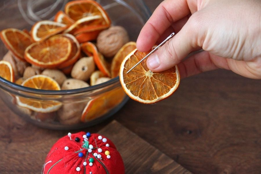 using a needle to poke holes through an orange slice for decorating