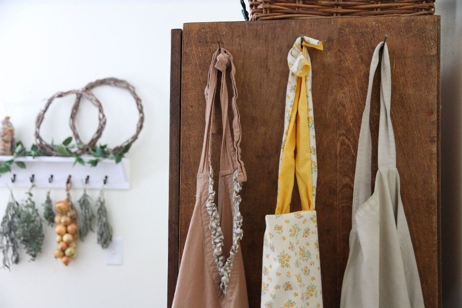 a row of aprons hanging on the side of a kitchen hutch