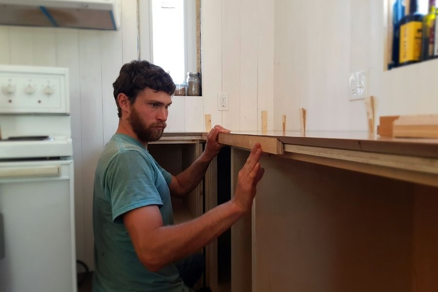 my man working to put the front edge on our hardwood kitchen countertops