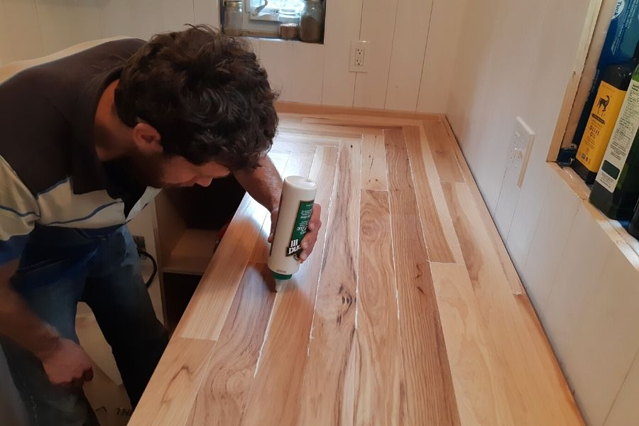 my man filling in hardwood kitchen counter cracks with waterproof glue