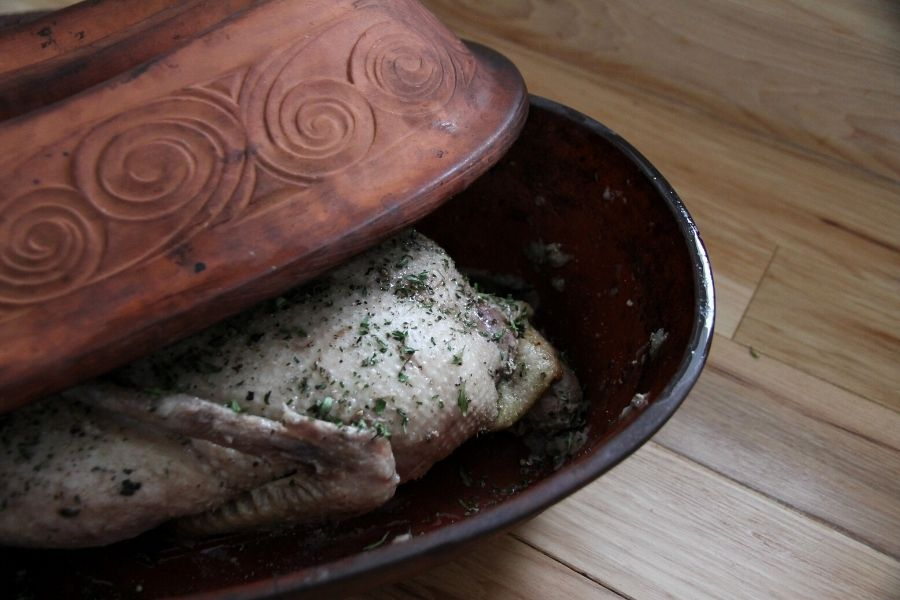 a young duck breast side up in the roasting pan, ready to be cooked