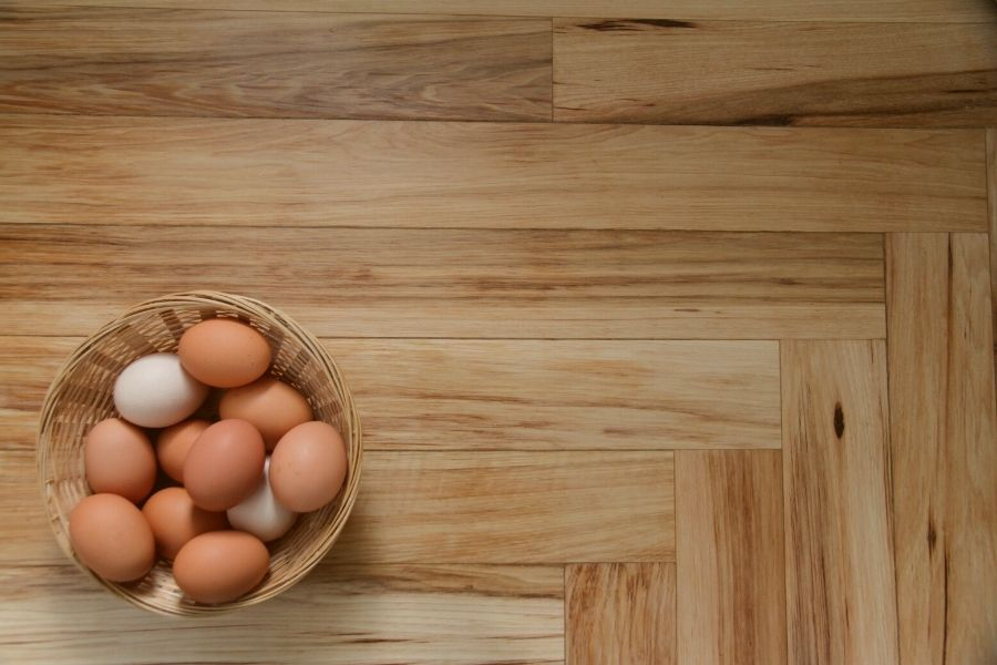 eggs in a basket on a kitchen counter where wood flooring intersects