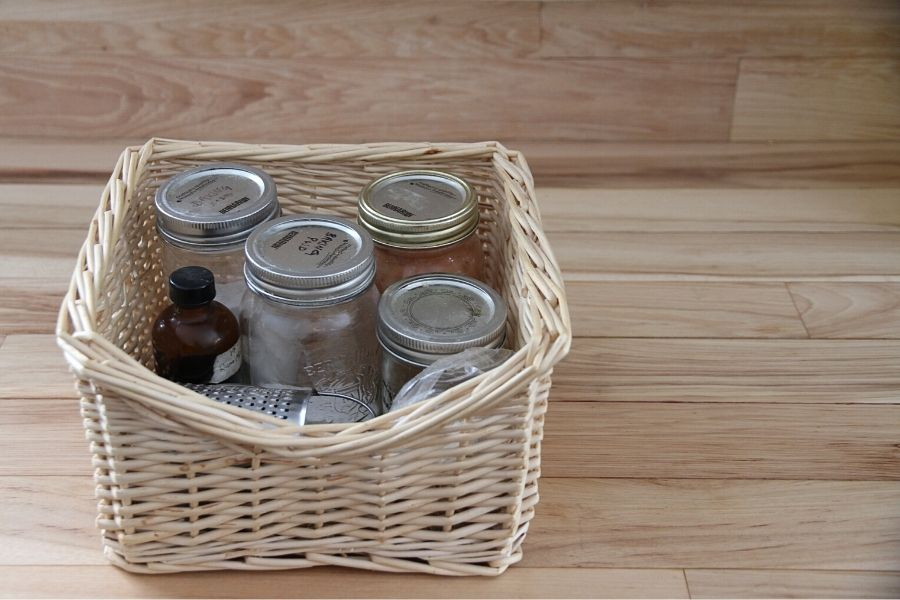 A basket of baking supplies that are stored in mason jars