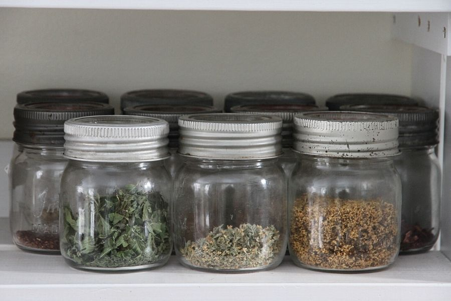 a row of small mason jars filled with tea and herbs