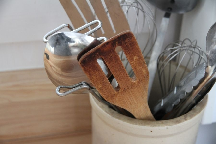 a small crock filled with stainless steel and wood cooking utensils
