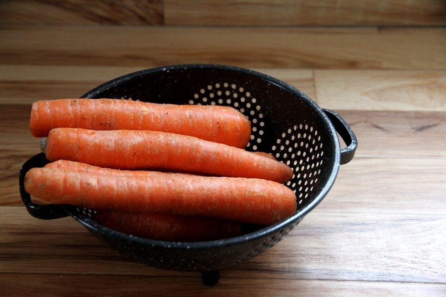 a black enamel stainless steel sieve filled with carrots