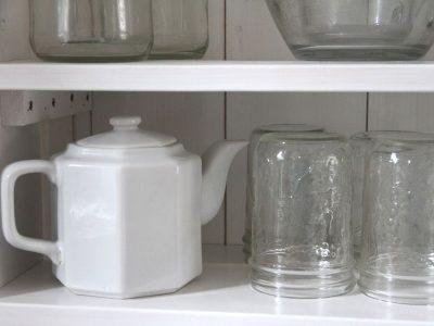 a white teapot sitting on an open kitchen shelf