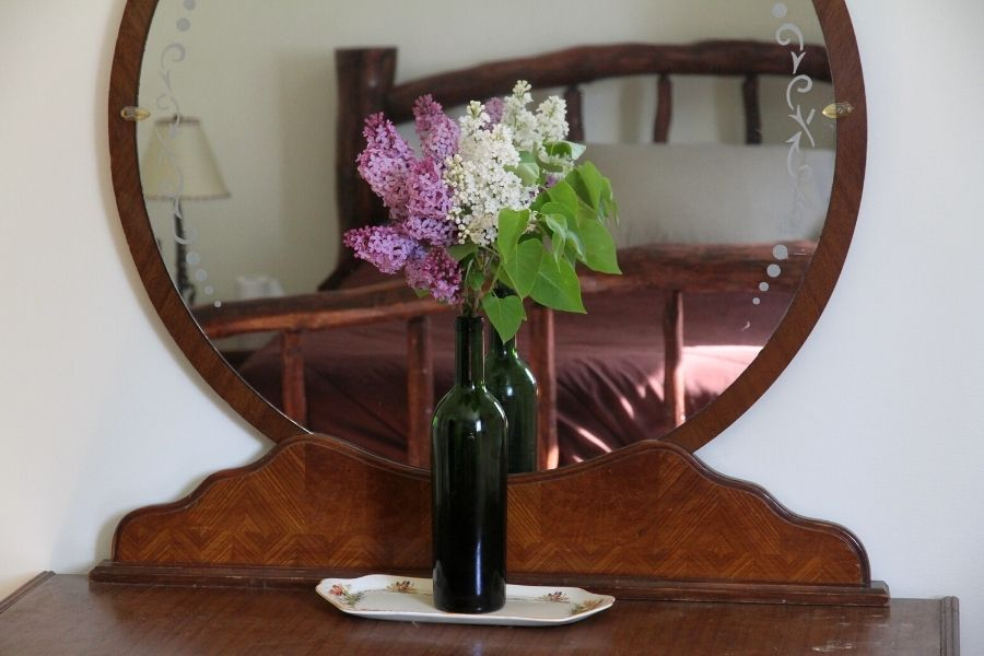 a green bottle filled with lavendar and white lilac blossoms