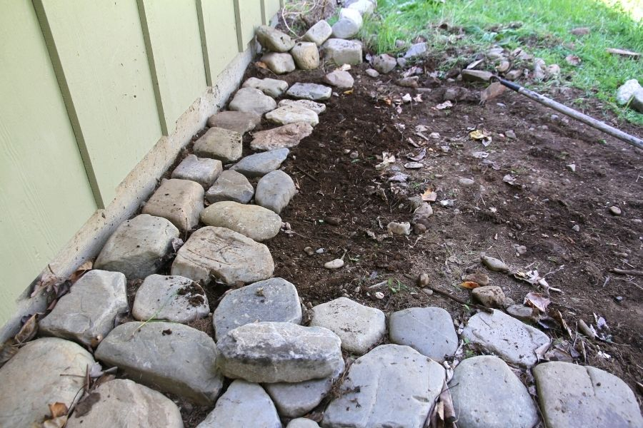 Round river rock lined up against the exterior house wall