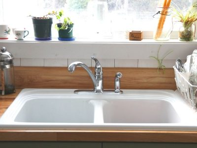 A white kitchen sink with a stack of clean dishes in the drying rack