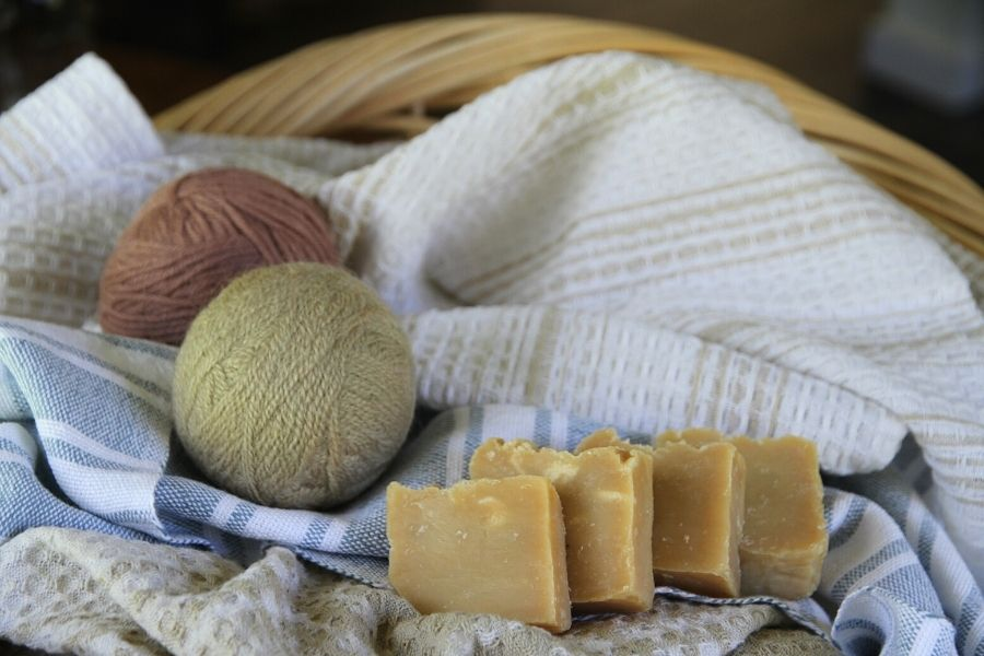 A basket of laundry with wool dryer ball and homemade soap bars